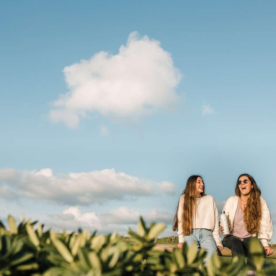 3 women standing on green grass field under blue sky