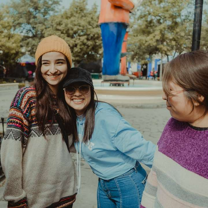 woman in gray sweater smiling beside girl in blue jacket
