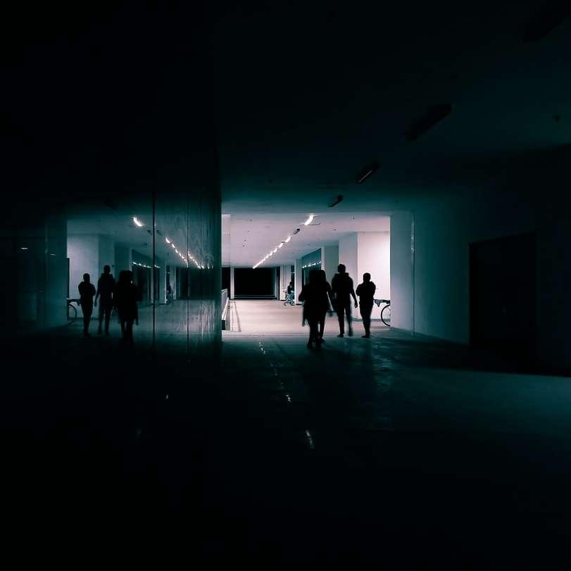 people walking on a blue lighted room
