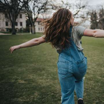 woman in blue denim jeans standing on green grass field