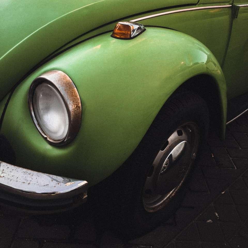 green volkswagen beetle on black brick floor