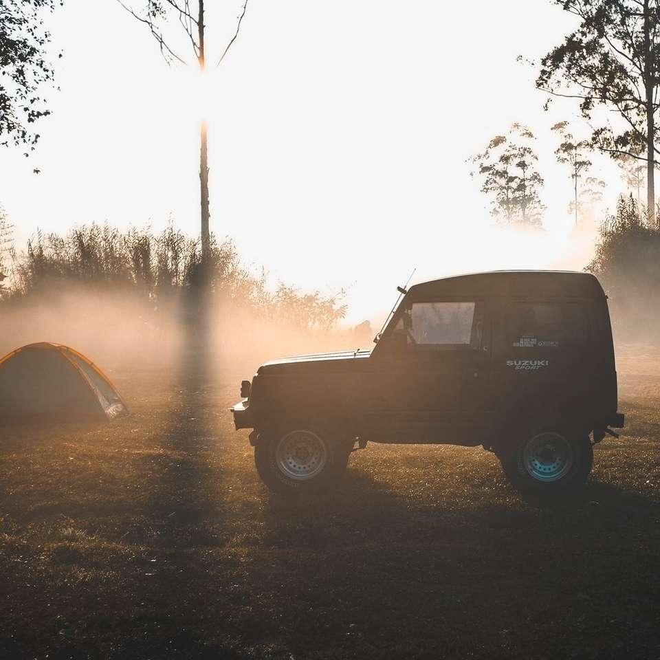 black vehicle near tent during daytime