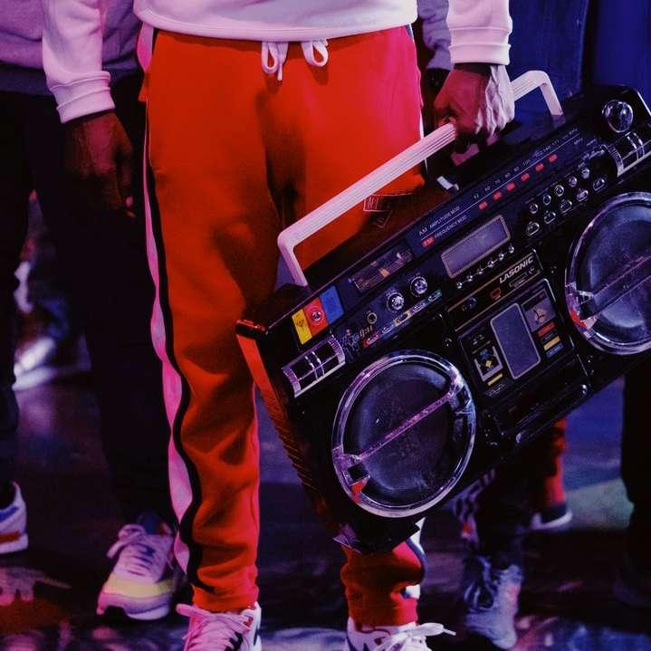 man in red jacket holding black dj controller