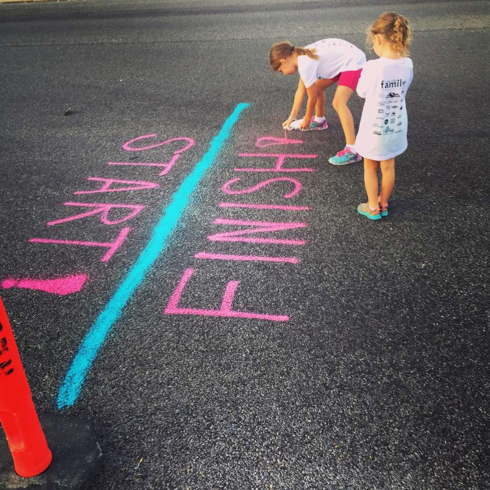 girl writing on the ground using a spray an