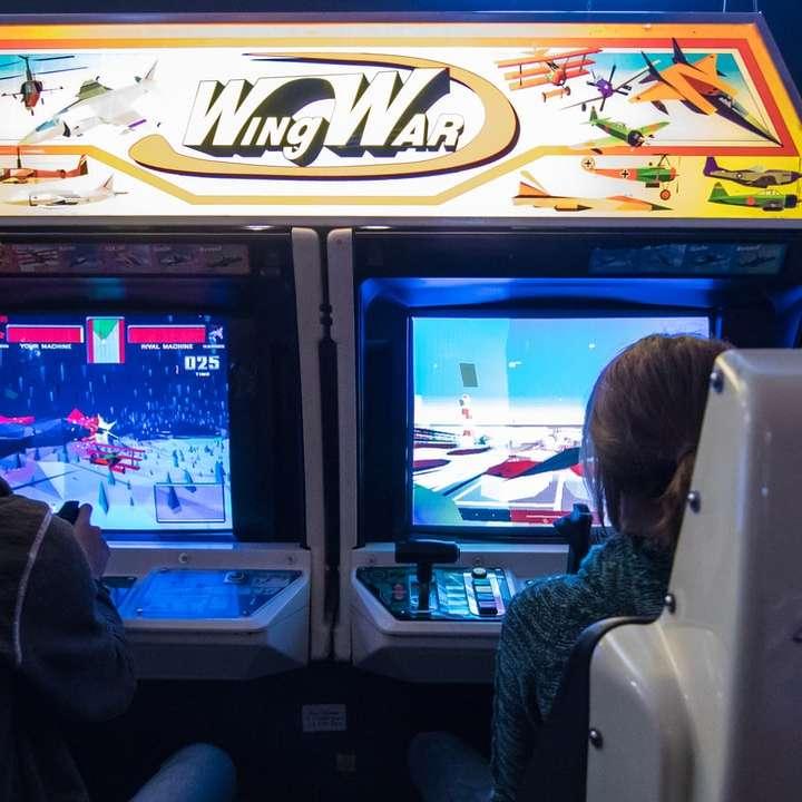man in black jacket watching on arcade game