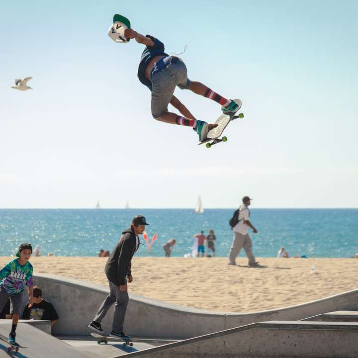 three people playing skateboard beside seashore