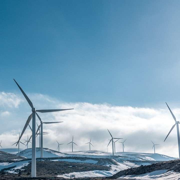 wind turbines on snowy mountain under clear blue sky