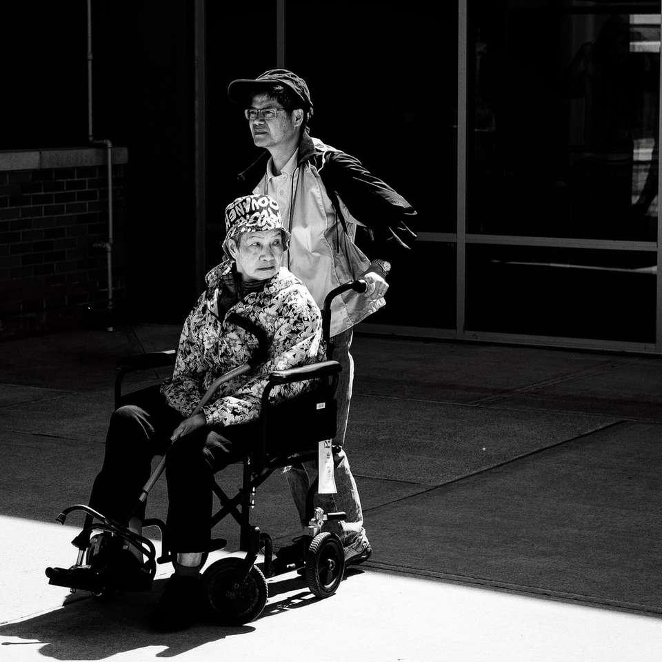 gray scale photo of man pushing wheelchair
