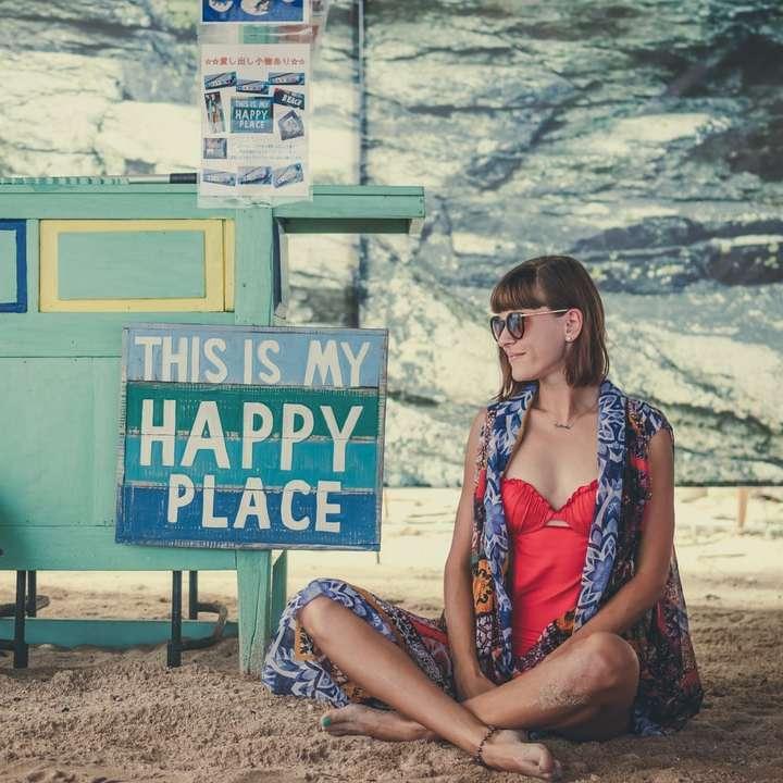 woman sitting on sand beside