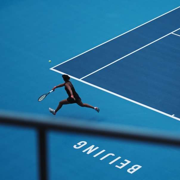 man playing tennis in court