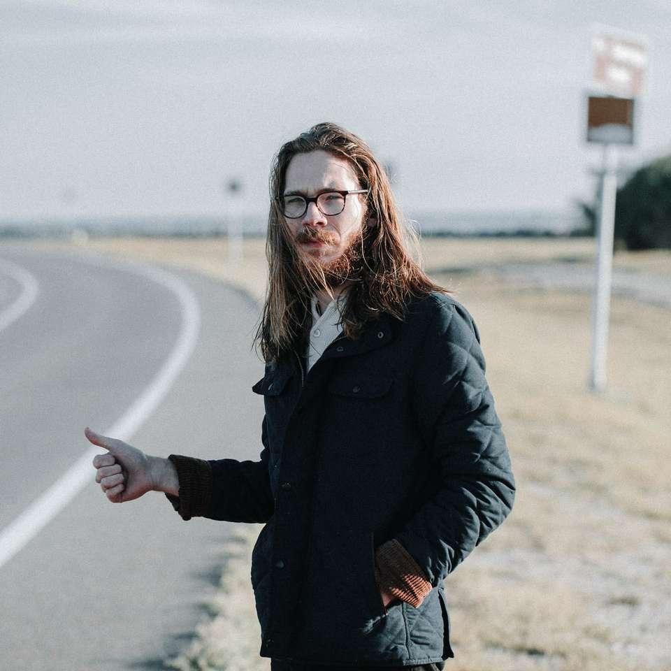 man standing near road during daytime